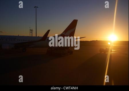 Qantas jets in silhouette on the tarmac at the Brisbane airport terminal Australia - Stock Photo