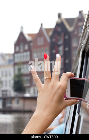 Tourist in a canal boat making pictures of Amsterdam - Stock Photo