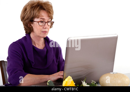 A mature woman who appears to be engrossed in whatever she sees on the screen of her laptop computer. - Stock Photo