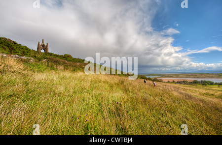 Children climb towards a Victorian Folly standing on a hill overlooking Lacken Strand in County Mayo, Ireland during - Stock Photo