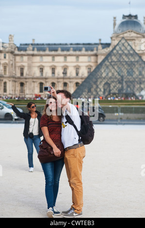 Paris, France - Young couple of tourists visiting town and taking photos of themselves by the Louvre Museum - Stock Photo