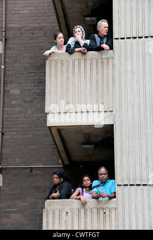 High rise housing estates with people out on balconies watching Notting Hill Carnival go by - Stock Photo