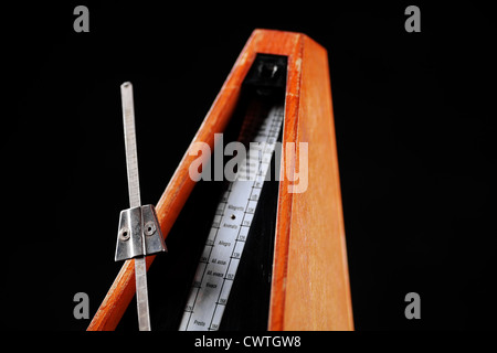 Vertical shot of a vintage metronome, on black - Stock Photo