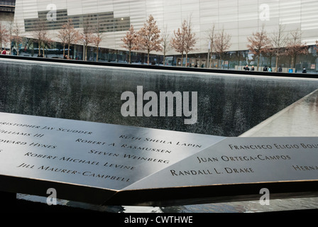National September 11 Memorial showing names on the parapet surrounding the pool and the Museum in the background. - Stock Photo