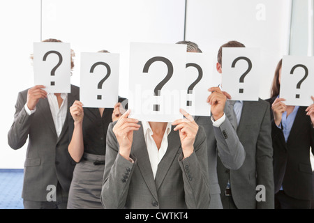 Businesspeople with question marks in front of their faces - Stock Photo