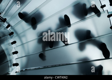 Feet walking on a glass staircase in the Apple NYC Fifth Avenue store. Feet are seen from underneath so silhouetted - Stock Photo