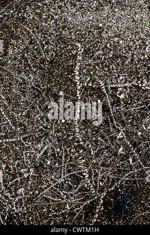Metal shavings or swarf from an industrial manufacturing process collected in a storage bin for recycling - Stock Photo