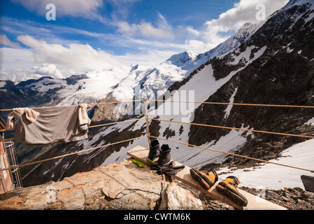 Climbers put out their tops, socks and boots to dry out in the warm afternoon sun outside the Mischabel Hut high - Stock Photo