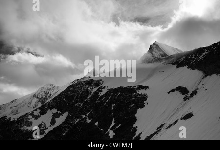 A black and white image of Taschhorn and Dom with bright sunshine illuminating the cloud around them. Saas Fee Switzerland. - Stock Photo