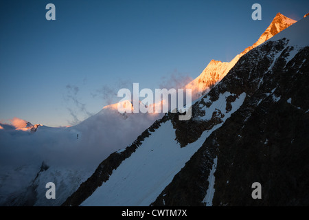 The summits of Alphubel, Taschhorn and Dom are illuminated by the sunrise. Saas Fee Switzerland. - Stock Photo