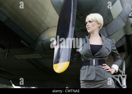 Young woman standing at propeller plane