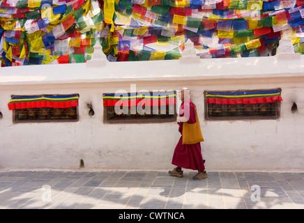 a monk walks around the stupa at the Boudhanath in Kathmandu, Nepal - Stock Photo