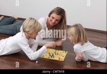 Mother and two children playing ludo on the floor - Stock Photo
