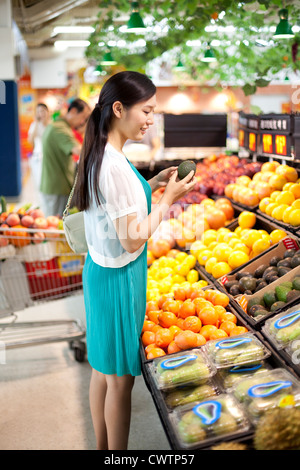 Young woman shopping in supermarket - Stock Photo