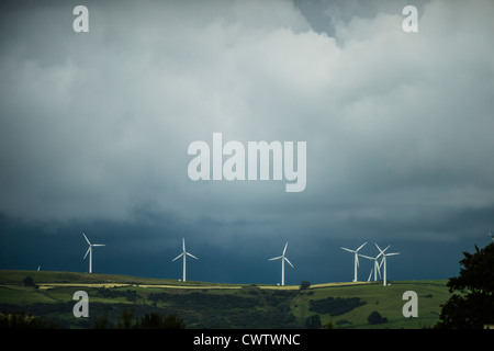 Dark clouds looking over the turbines of a wind farm outside Bridgend south wales UK - Stock Photo