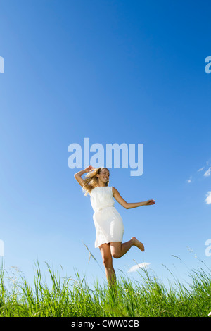 Smiling woman walking in tall grass - Stock Photo