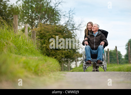 Woman pushing father in wheelchair - Stock Photo