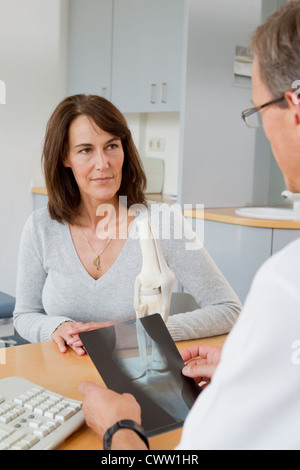 Doctor examining x-rays with patient - Stock Photo