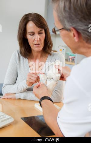 Doctor showing patient model of bones - Stock Photo
