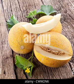 Melon with slices and leaves on a old wooden table. - Stock Photo