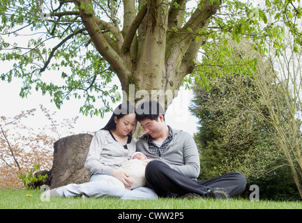 Parents holding sleeping baby in park - Stock Photo