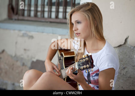 Blond young woman playing electric guitar - Stock Photo