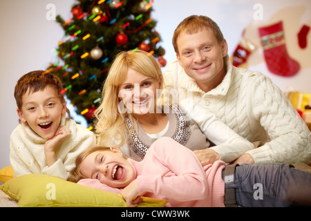 Portrait of four happy family members at home on Christmas Eve - Stock Photo