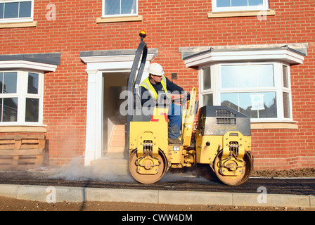 Hard landscaping in progress on a new residential development in South East England. Man driving a roller on asphalt - Stock Photo