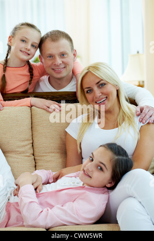Portrait of happy couple and two daughters looking at camera - Stock Photo
