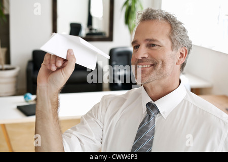 Businessman playing with paper airplane - Stock Photo