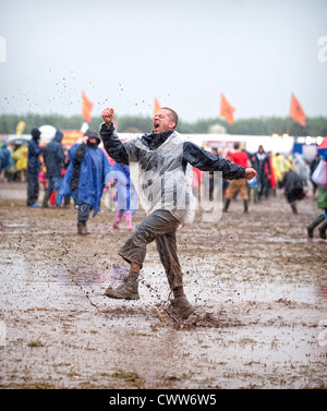 Music fan dancing in the mud at the main stage during T In The Park Festival at Balado on July 8, 2012 in Kinross