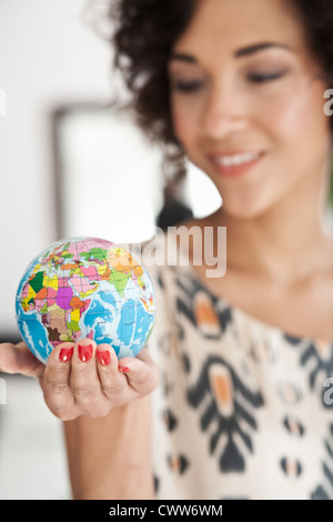 Businesswoman holding miniature globe - Stock Photo