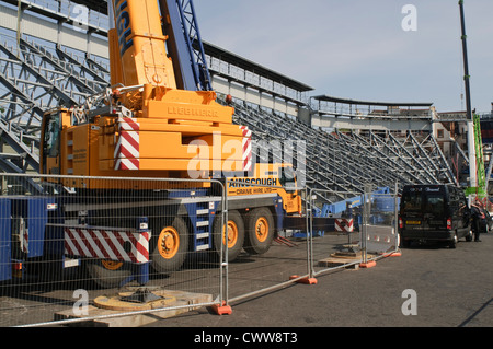 Construction crane dismantling temporary seating after the Edinburgh Military Tattoo - Stock Photo