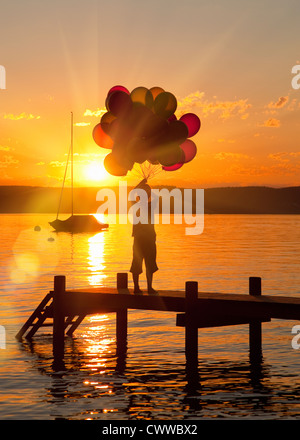 Boy holding balloons on wooden dock - Stock Photo