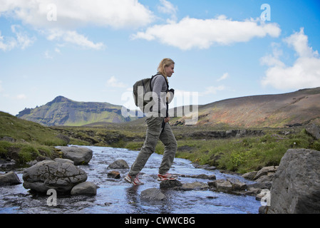 Hiker crossing rocky rural stream - Stock Photo