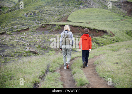 Mother and daughter hiking on hillside - Stock Photo