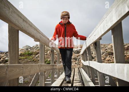 Girl walking on wooden foot bridge - Stock Photo
