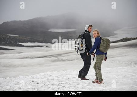 Hikers walking in snowy landscape - Stock Photo
