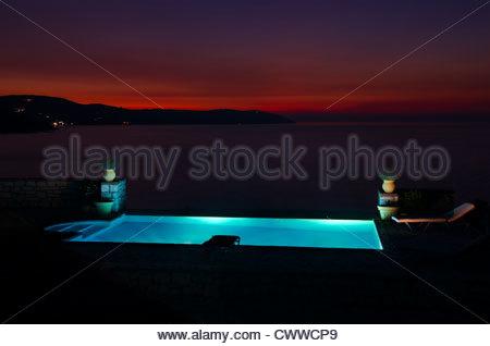 Twilight sunset over pool and sea - Stock Photo