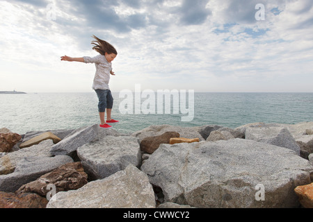 Girl playing on rocks at beach - Stock Photo