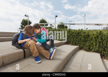 Children talking on steps outdoors - Stock Photo