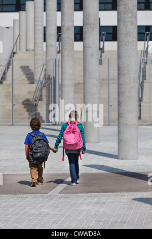 Children holding hands in courtyard - Stock Photo
