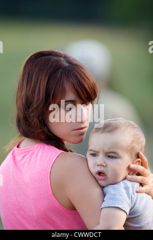 Mother holding crying baby outdoors - Stock Photo