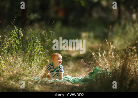 Toddler sitting on blanket in field - Stock Photo