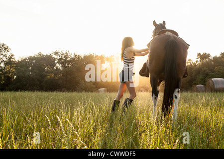 Woman saddling up horse in field - Stock Photo