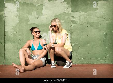 Teenage girls sharing headphones - Stock Photo