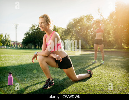 Runners stretching on grass in park - Stock Photo