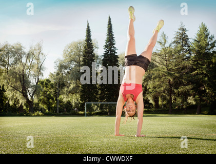 Woman doing cartwheel in park - Stock Photo