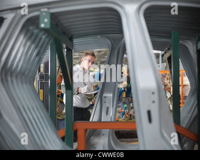 Worker inspecting car parts in car factory - Stock Photo