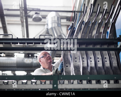 Worker with car parts in car factory - Stock Photo